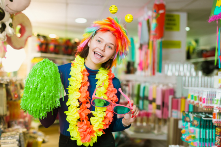 Cheerful young female having fun in festival outfits store while preparing for party