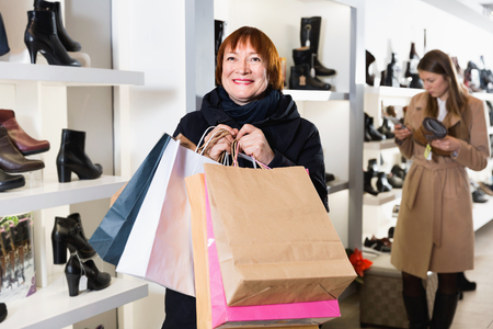 Portrait of adult happy positive smiling woman which is showing purchases in shoes store. 写真素材