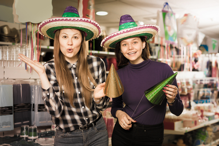 Portrait of nice comically dressed girls joking in festive accessories shop