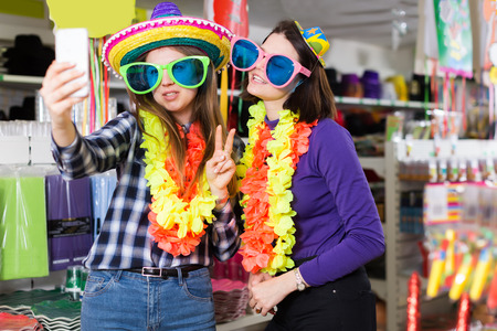 Two cheerful female friends taking selfie in festive things store while preparing for party