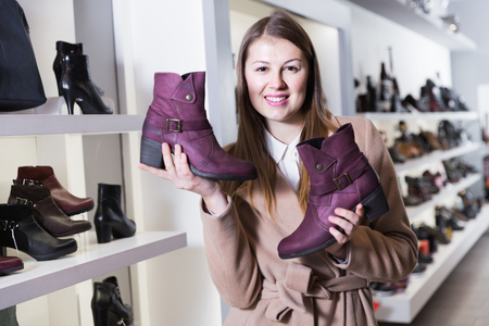 Smiling girl is demonstraiting autumn shoes in shoes shop.