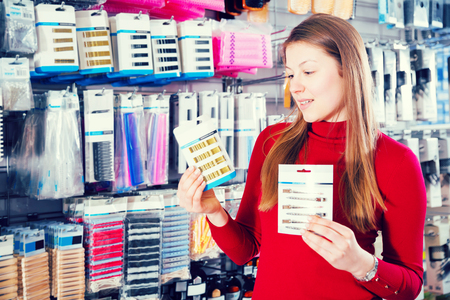 Young woman is choosing modern decorations for her hair in the store.