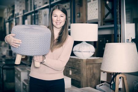 portrait of smiling woman buyer choosing pouf in furniture shop