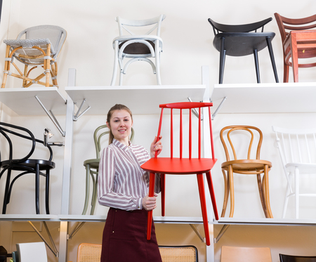 Young polite saleswoman offering original wooden chairs in furniture store