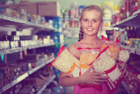 Girl 9-15 years old is standing with packets of popcorn in the supermarket. Stockfoto