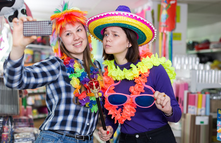 Two cheerful young female friends taking selfie in festive things store while preparing for party