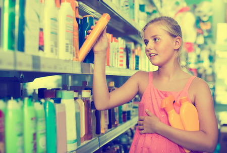 positive teenager girl choosing bottles of sun protection indoors in the shop Фото со стока - 122633936
