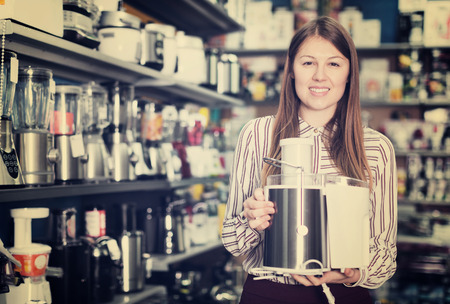 Positive salesgirl suggesting kitchen machine in store of household appliances 写真素材