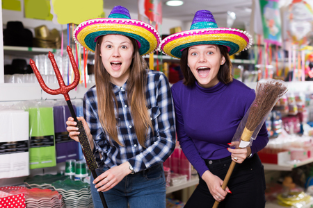 Portrait of pretty comically dressed girls joking in festive accessories shop Banco de Imagens