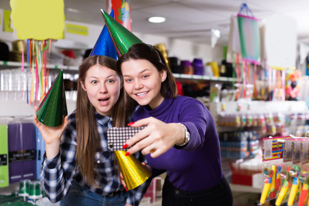 Comically dressed happy girls making funny selfies photo in festive accessories shop