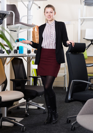 Full length portrait of young attractive saleswoman welcoming visitors to chair store 版權商用圖片