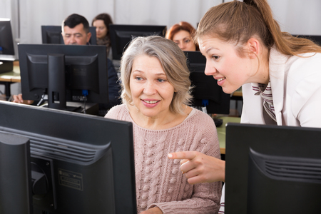 Friendly young female teacher helping smiling mature woman to use computer in classroom