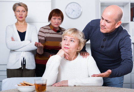 Mature female is sitting upset and man is apologizing at home.