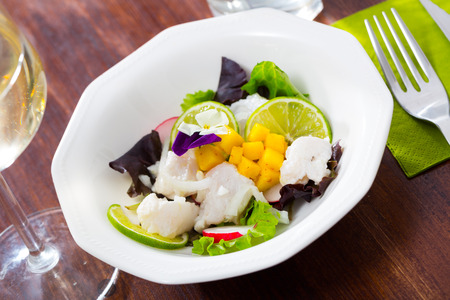Cod ceviche with mango, lime and greens served on plate Stock Photo
