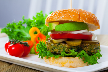 Juicy veggie burger with falafel, fresh tomatoes, onion, pickled cucumbers and ripe avocado on white plate with vegetables