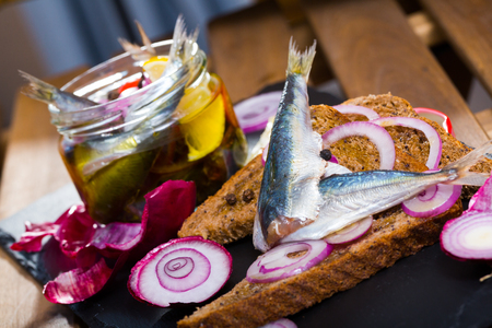 Anchovies of home salt pickling in marinade of vinegar, lemon, olive oil and sea salt with red onions and assorted peppercorns served on rye bread Archivio Fotografico