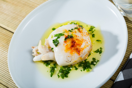 Plate of roasted Cuttlefish served with olive oil and garlic sauce and greens