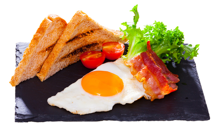 Delicious breakfast of fried eggs with bacon, bread and vegetable garnish on black serving board. Isolated over white background