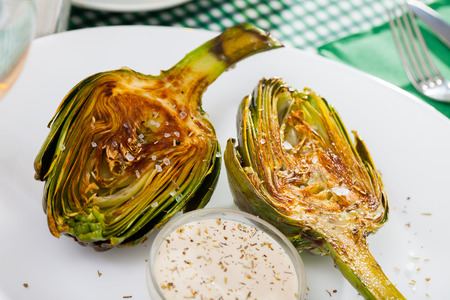 Appetizing roasted halves of artichokes served with coarse salt and sauce