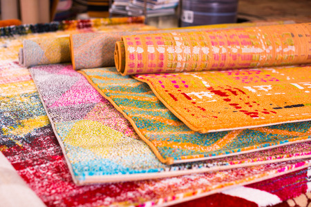 Various colorful wool rugs for sale at store, no people Stock Photo