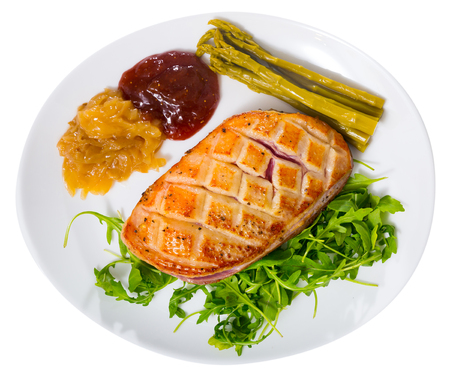 Tasty grilled duck magret fillet served with greens, onion and cranberry sauce. Isolated over white background