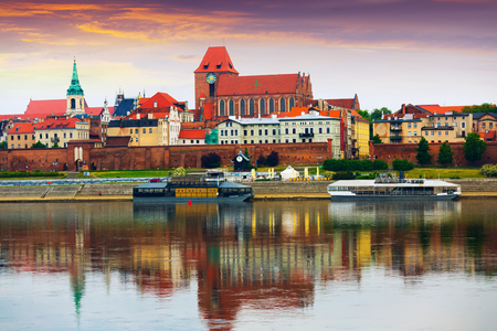 View of Torun city with Catholic church of Saints John Baptist and John Evangelist across Vistula at sunset, Poland