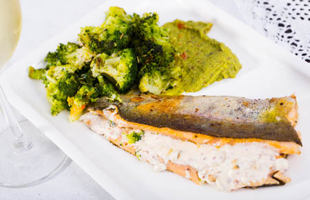 Delicious fried brook trout fillets with broccoli served with glass of wine Stock Photo
