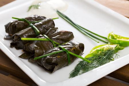 Tasty  grape rolls made from grape leaves, dish of Bulgarian cuisine Sarni at plate Stock Photo