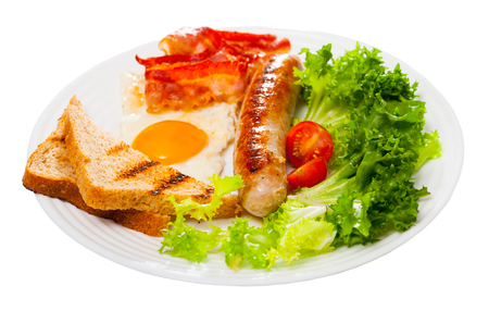 American breakfast. Tasty fried egg, sausage, bacon and grilled bread served with cherry tomatoes and greens. Isolated over white background