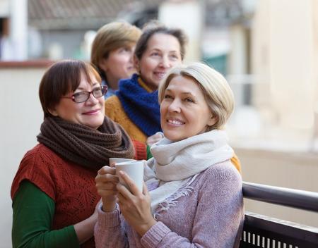 Femmina senior positiva in vestiti caldi che mangiano tazza di tè caldo sul terrazzo. Focus sulla donna bionda