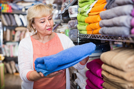 Glad cheerful positive  mature woman holding cotton colour towel in the textile shop Фото со стока - 122716141