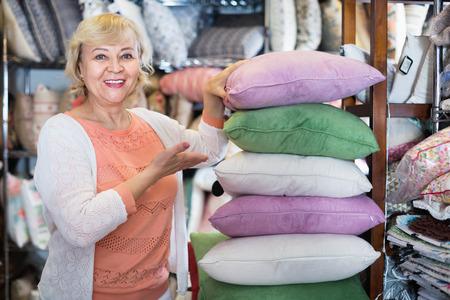 Glad pleasant  female buyer choosing colour pillows in the textile store 版權商用圖片