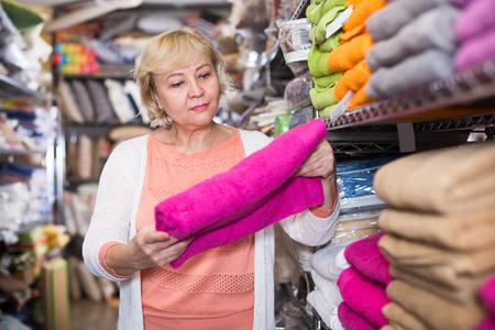 portrait of elderly woman consumer with bath towel in the shop Фото со стока - 122716242