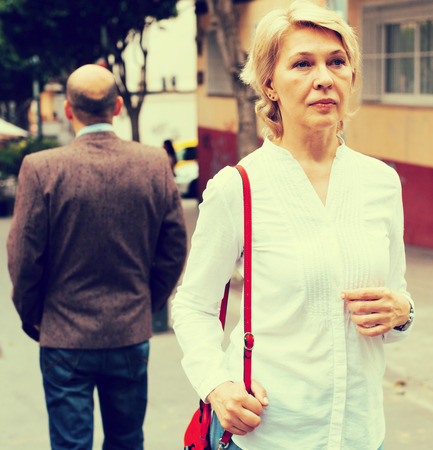 Portrait of annoyed mature woman standing away from man standing back to her
