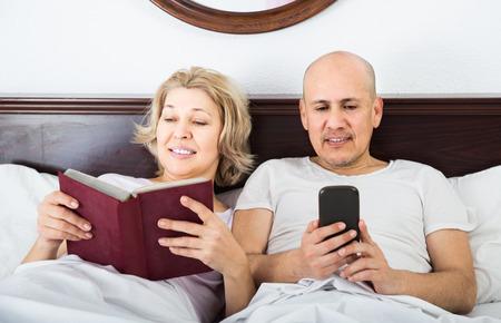 Positive european mature couple reading with smartphones in bedroom interior
