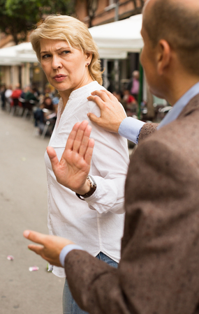 annoyed retiree woman stopping dialog by hand gesture outdoors