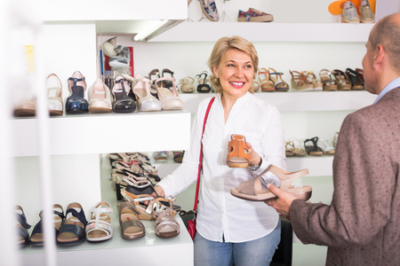 portrait of mature woman holding picked pair of shoes in boutique