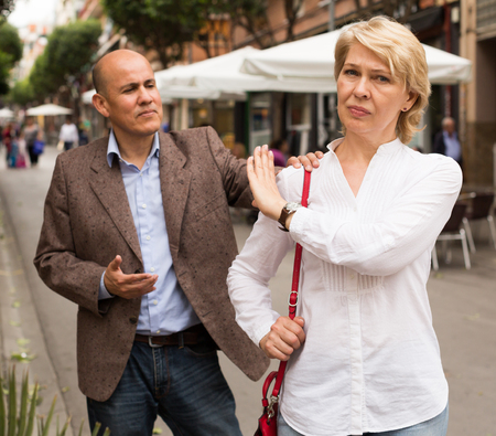 Portrait of annoyed mature woman standing away from arguing man outdoors Фото со стока