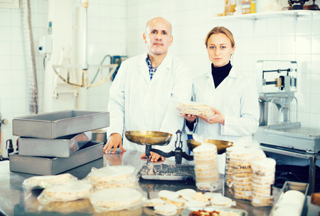 Positive couple standing with box of turron in production workshop 版權商用圖片