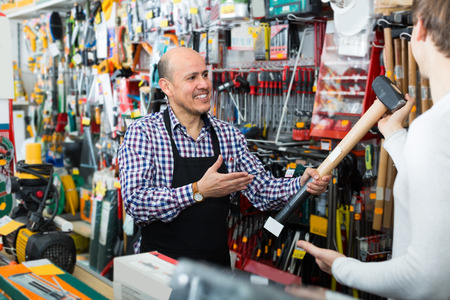 european salesman showing different tools and instruments in supermarket 写真素材