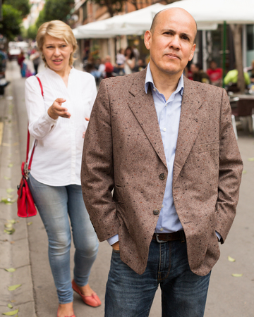 closeup of angry retiree man being sad with woman standing outdoors Banco de Imagens