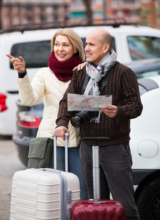 Elderly spouses with baggage and paper map outdoors
