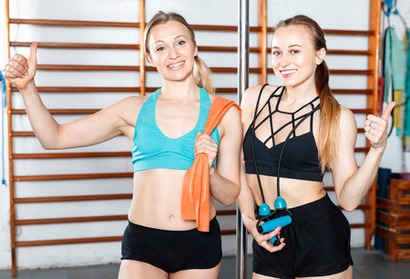 Two attractive young positive smiling women taking break during workout at gym, posing together Standard-Bild - 123022833