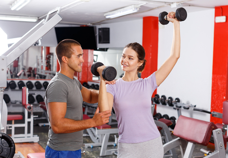 Young woman doing exercises with dumbbells with help of trainer at gym Standard-Bild - 123022922