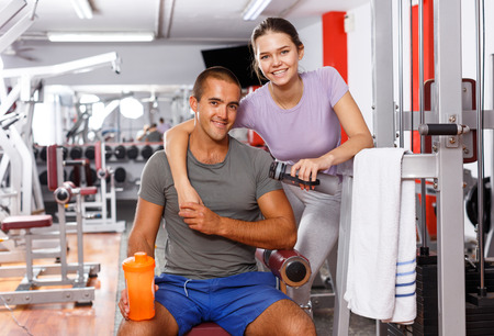 Young positive man and woman posing sitting on equipment at gym