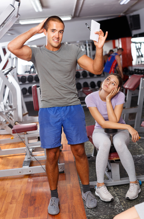 Personal trainer discussing workout plan with young woman at gym