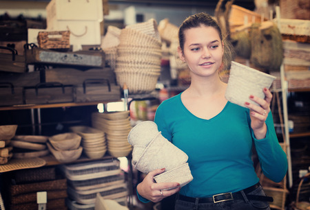 Smiling young woman consumer holding wicker basket in decor items store