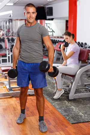 Portrait of muscular guy lifting dumbbells at gym