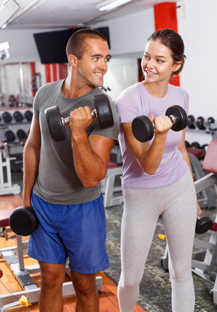 Young positive man and woman posing with dumbbells at sports club