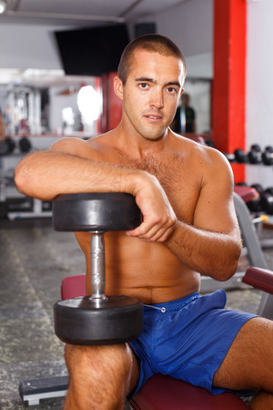 Portrait of muscular guy with naked torso lifting dumbbells at gym
